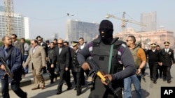 Seorang polisi dengan menggunakan masker mengawal kepala keamanan Kairo, Osama al-Saghir (tiga dari kiri) saat berada di Lapangan Tahrir, pusat pergolakan tahun 2011 di Kairo, Sabtu (25/1).