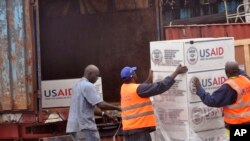 American Aid goods are loaded onto a truck after it arrived by airplane, to be used in the fight against the Ebola virus spreading in the city of Monrovia, Liberia, Aug. 24, 2014.