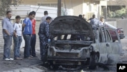 People gather at the scene of a bomb attack in Baghdad, 10 Nov 2010