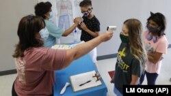 Texas ျပည္နယ္ Wylie ၿမိဳ႕က အထက္တန္းေက်ာင္းတခုမွာ ကိုယ္အပူခ်ိန္ တိုင္းေပးေနတဲ့ ဆရာမတဦး။ (ဇူလိုင္ ၁၄၊ ၂၀၂၀)