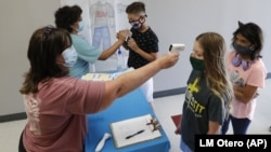 Amid concerns of the spread of COVID-19, science teachers Ann Darby, left, and Rosa Herrera check-in students before a summer STEM camp at Wylie High School Tuesday, July 14, 2020, in Wylie, Texas. (AP Photo/LM Otero)