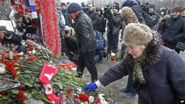 People lay flower tributes at a bus stop in Moscow to commemorate Yegor Sviridov, a soccer fan of the Russian club Spartak who was killed in an attack on soccer supporters 40-days ago, during a rally at a bus stop in Moscow, Russia, 15 Jan 2011