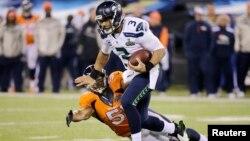 2014年2月2日新泽西州东卢瑟福四十八届超级碗足球比赛: 西雅图海鹰队的拉塞尔·威尔逊挣脱丹佛野马队列侬的擒抱。