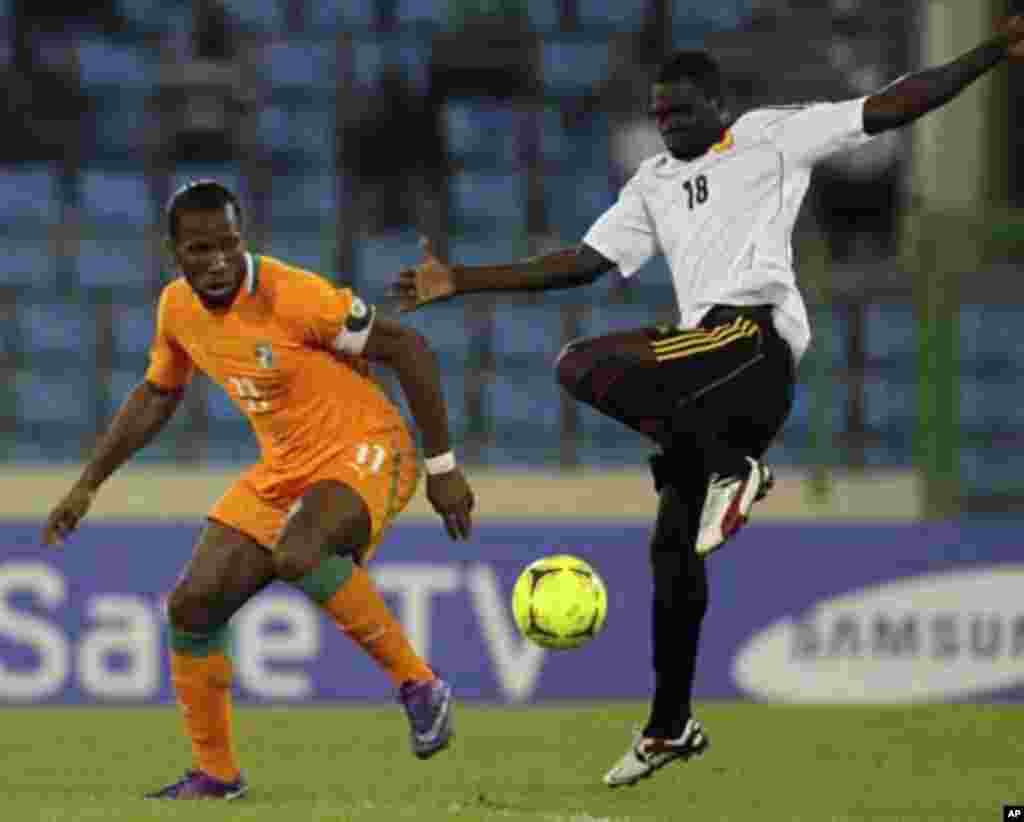 Didier Drogba (L) of Ivory coast fights for the ball with Cabungula Arsenio Sebastiao of Angola during their African Nations Cup soccer match in Malabo January 30, 2012.