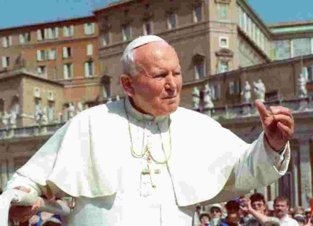 El Papa Juan Pablo II saluda a los peregrinos que llegan a la plaza de San Pedro, en el Vaticano, durante su audiencia semanal de los miércoles (1998).