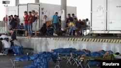 Para migran yang diselamatkan di Austria dekat perbatasan dengan Hungaria menunggu di kamp darurat di Nickelsdorf, Austria, 29 Agustus 2015.