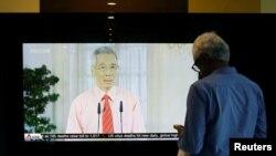 စကၤာပူ ၀န္ႀကီးခ်ဳပ္ Lee Hsien Loong ရဲ႕ ေျပာၾကားခ်က္ကို ရုပ္သံလိုင္း တခုကေန ၾကည့္ရႈေနတဲ့ အမ်ိဳးသားတဦး (ဧၿပီ ၀၃၊ ၂၀၂၀)