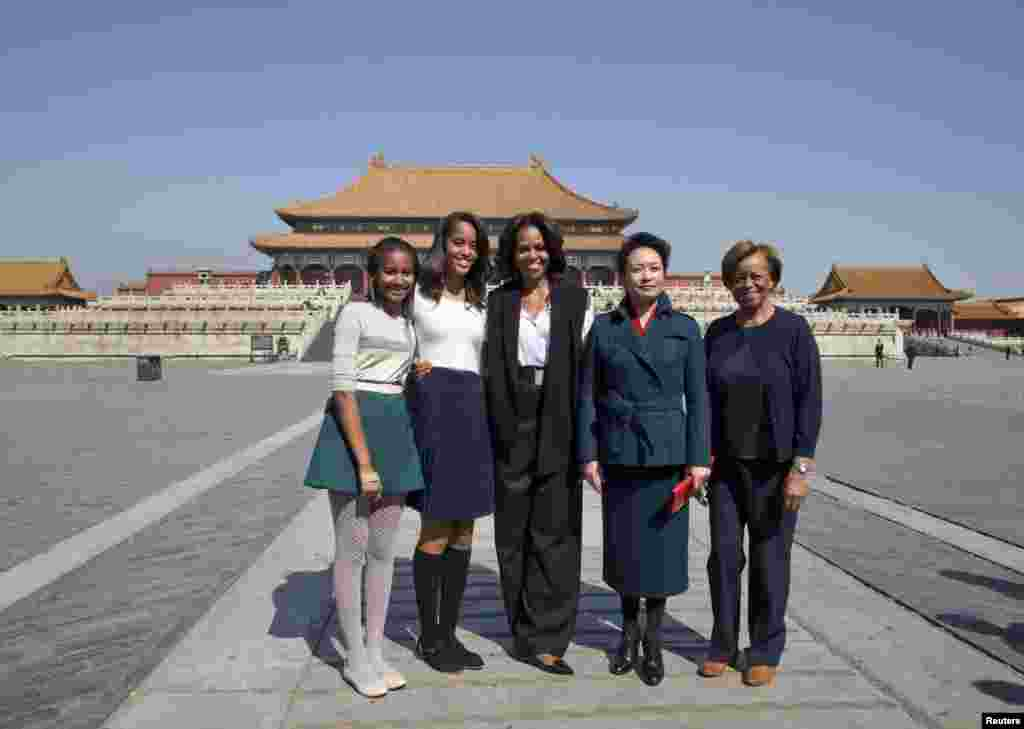 U.S. first lady Michelle Obama, her daughters Sasha and Malia and her mother Marian Robinson pose with Peng Liyuan, wife of Chinese President Xi Jinping, as they visit Forbidden City in Beijing, March 21, 2014.
