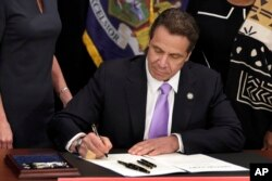 FILE - New York Gov. Andrew Cuomo signs a law that will gradually raise New York's minimum wage, April 4, 2016. New York joins 18 other states by raising its minimum wage in 2017.
