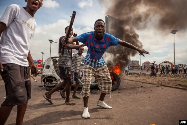 FILE - Demonstrators gather in front of a burning car during an opposition rally in Kinshasa, DRC, Sept. 19, 2016.