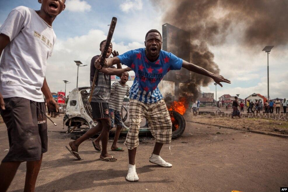 민주콩고공화국 킨샤사에서 반정부 시위대가 불 붙은 자동차 앞에 모여있다. 수십명의 시위대는 조셉 카빌라 대통령이 올해 안에 물러날 것을 요구했고, 경찰은 이들을 해산시키기 위해 최루탄을 발사했다.