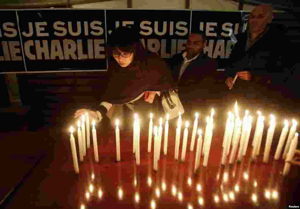 "Candles are placed in front of a banner that reads ""I am Charlie"" at the French Embassy in Hanoi, Vietnam, Jan. 8, 2015."