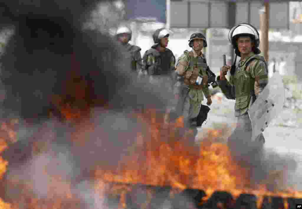Afghan police stand by burning tires during an anti-Islam film protest, in Kabul, Afghanistan, Sept. 17, 2012.