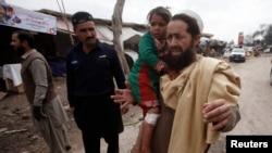 Một người dân bế con gái của ông bị thương trong vụ nổ bom ở ngoại ô Peshawar, Pakistan, 14/3/2014