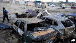 Seorang polisi memeriksa lokasi ledakan bom di lapangan parkir sebuah dealer mobil bekas di Habibiya, Baghdad, Irak (16/4).