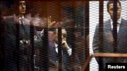 Cựu Tổng thống Ai Cập Hosni Mubarak vẫy chào người ủng hộ từ sau song sắt tại phòng xử án ở học viện cảnh sát, ngoại ô Cairo, ngày 9/5/2015.