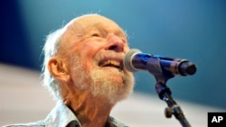 FILE - Pete Seeger performing on stage during the Farm Aid 2013 concert at Saratoga Performing Arts Center in Saratoga Springs, N.Y.