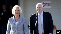 U.S. Sen. John McCain, R-Ariz., and his wife, Cindy McCain, leave a polling station after voting, Tuesday, Aug. 30, 2016.