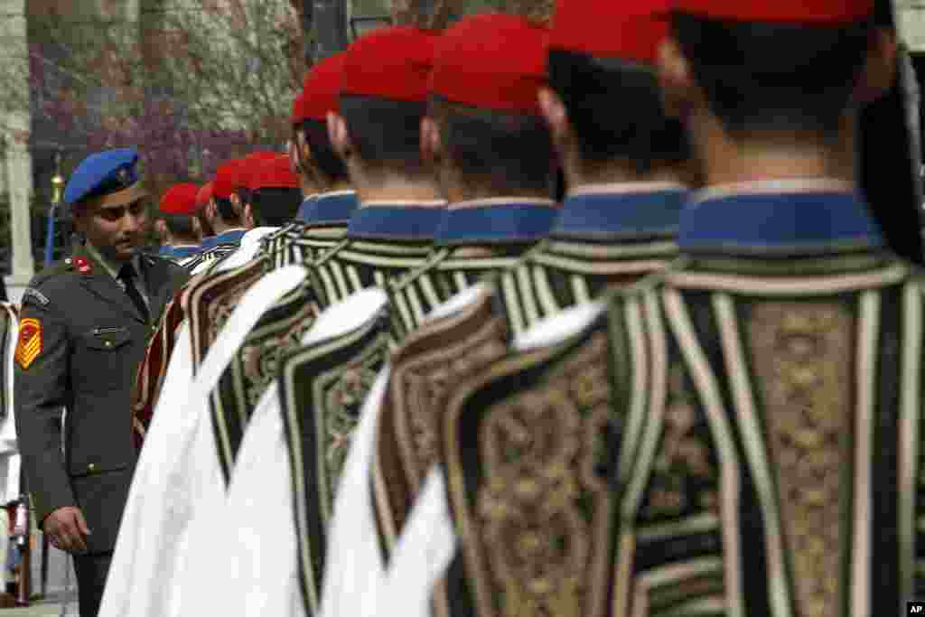 A military officer inspects Greek Presidential guards prior to a parade to commemorate Independence Day. For the second straight year, heavy police presence, for fear of disruptive incidents, has effectively closed off central Athens.