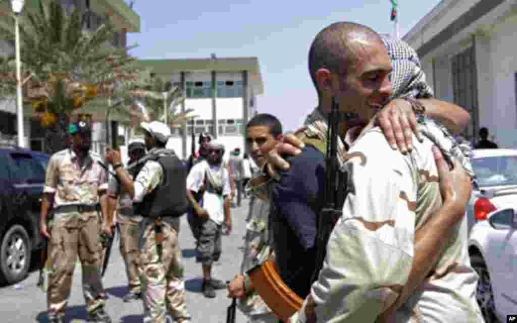 2011年8月22日,利比亚反政府武装士兵在的黎波里从前的女兵军营相互拥抱。反政府武装在对的黎波里发动闪电式进攻之后,星期一宣布控制了利比亚首都的大部分地区,显示统治利比亚42年的卡扎菲行将倒台。不过,零星的战斗仍不时发生,卡扎菲也去向不明。(AP)