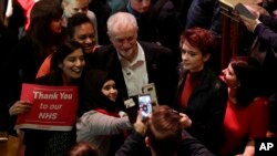 The leader of Britain's opposition Labour party Jeremy Corbyn poses with supporters after his speech at a rally to demand the government introduce an emergency budget for the National Health Service (NHS) to end a winter crisis, at Methodist Central Hall in London, Thursday, Jan. 25, 2018.
