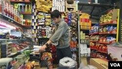Seorang warga Iran, Jafar Rahimi, bekerja di toko bahan makanannya setelah pengumuman kenaikan harga roti di negara ini, Selasa (26/4).