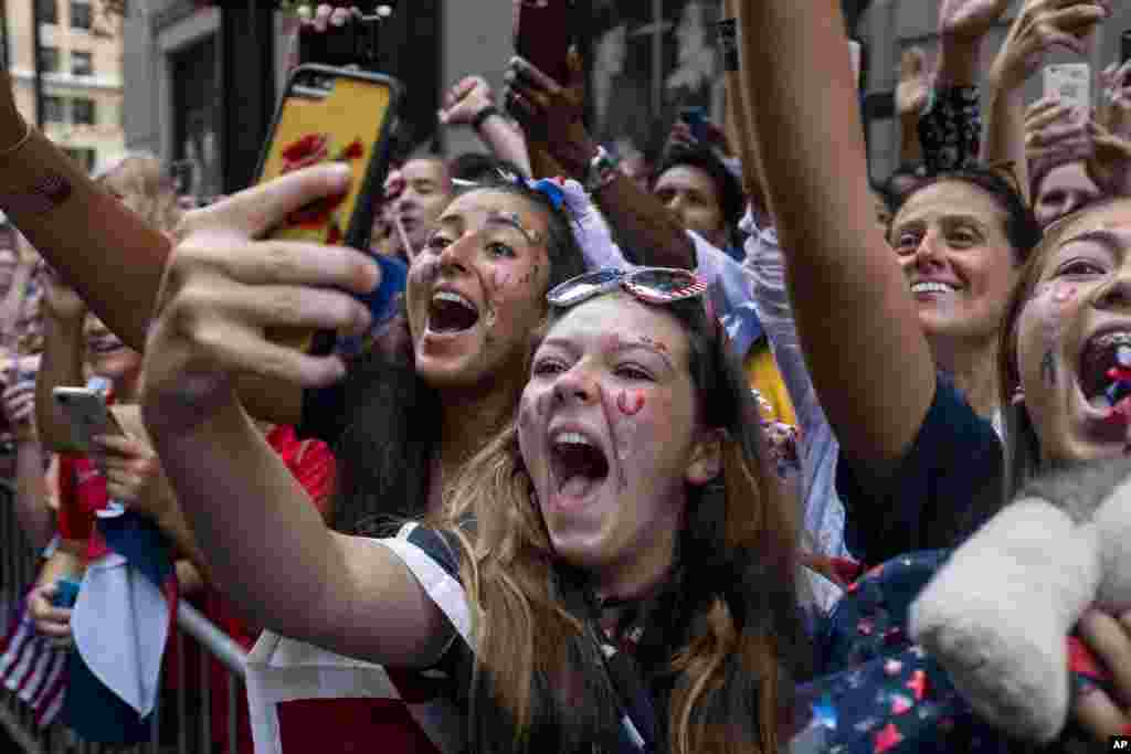 Fans celebrates as members of the the U.S. women's soccer team pass by during a ticker tape parade along the Canyon of Heroes in New York. The U.S. national team beat the Netherlands 2-0 to capture a record fourth Women's World Cup title.