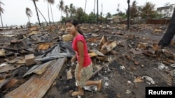 A girl walks at the site of her house, which was burned during recent violence in Sittwe, June 16, 2012.