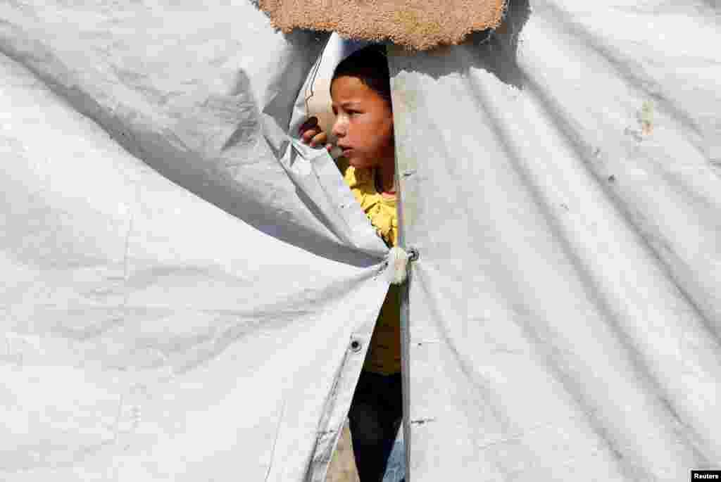 یک کودک جنگ زده و گریخته از دست داعش در یک کمپ با دوستانش بازی می کند.