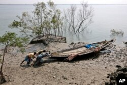 FILE - Villagers help a fisherman couple push their boat to the water at Satyanarayanpur village in the Sundarbans, India. A report says Asia will endure extreme heat, rising sea levels, growing losses from severe weather and increasing food insecurity in coming decades as climate change raises temperatures and alters weather patterns across the globe.