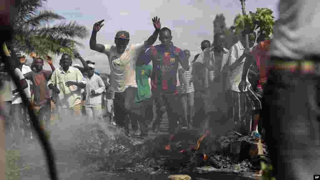Scandant «passons!», des manifestant forcent une barricade dans le quartier de Musaga de Bujumbura, au Burundi, le lundi 4 mai 2015.