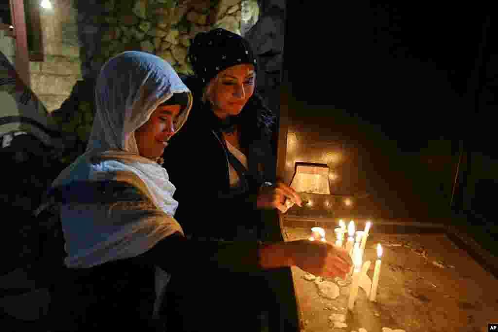Христиане в Ираке зажигают свечи после рождественской мессы в церкви Святого Иосифа в Багдаде, 24 декабря 2017