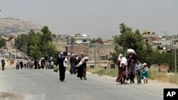 FILE- Syrians carry food as they return to the rebel-held Damascus suburb of Moadamiyeh near Damascus, July 14, 2014.