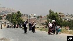 Dân chúng Syria mang các bao lương thực trở lại vùng ngoại ô Moadamiyeh do phe nổi dậy kiểm soát sau khi tổ chức Trăng lưỡi liềm Đỏ chở 1.000 bao lương thực đến để phân phối dưới sự giám sát của Liên hiệp quốc