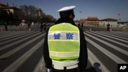 一名警察在北京的人民大会堂外等待人大代表到来。(2012年3月11日)
