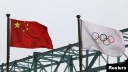 中國國旗和奧運旗幟在北京冬奧組委會外飄揚。(2021年3月30日)