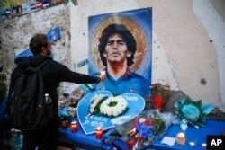 """Seorang pria memegang lilin untuk menghormati meninggalnya legenda sepak bola Diego Maradona, di """"Quartieri Spagnoli"""", Naples, Kamis, 26 November 2020."""