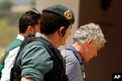 Former President of the Spanish Football Federation Angel Maria Villar, right, is lead by Spanish Civil Guard policeman to enter the Federation headquarters during an anti-corruption operation in Las Rozas, outside Madrid, July 18, 2017.