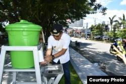 Bupati Poso Darmin Agustinus Sigilipu memeriksa salah satu fasilitas tong air yang didirikan di taman terbuka hijau kota poso untuk memudahkan masyarakat mencuci tangan. (Foto: Humas Pemkab Poso)