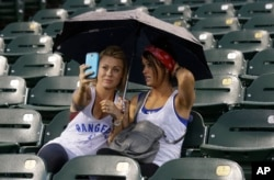These two baseball fans take selfies under an umbrella during a rain delay of a game between the Texas Rangers and Seattle Mariners Sept. 2014, in Texas. (AP Photo/LM Otero)