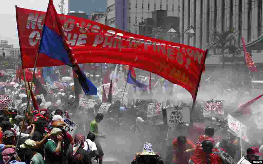 """Police use a water cannon on """"Bayan Muna"""" (My Country First) activists who tried to march to the U.S. embassy protestingPresident Barack Obama's visit, Manila April 29, 2014."""