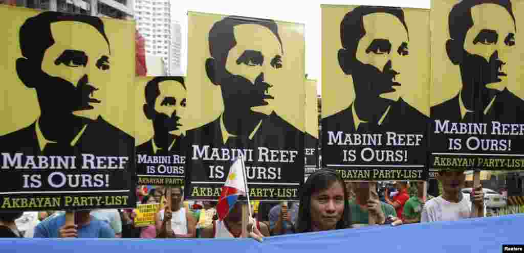 Protesters display placards with images of national hero Apolinario Mabini as they march to the Chinese consulate office in Manila, June 12, 2014.
