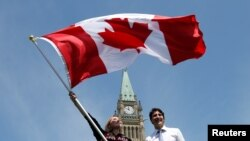Une sportive canadienne tient le drapeau national près du Premier ministre Justin Trudeau au Parliament Hill à Ottawa, Ontario, Canada, le 21 juillet 2016.