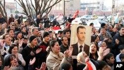 親敘利亞政權的示威者星期四在霍姆斯高舉總統阿薩德的圖像﹐高喊支持口號。