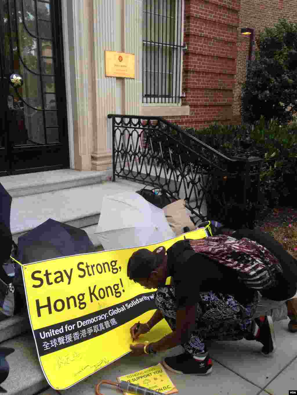 Supporters of Hong Kong's pro-democracy movement sign a banner outside the Hong Kong Economic & Trade Office in Washington, Oct. 1, 2014. (Michael Lipin/VOA)