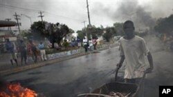 A man pushes a wheelbarrow past a barricade of burning tires in Port-au-Prince, Haiti, Thursday Dec. 9, 2010