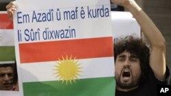 """Seorang Kurdi dalam sebuah protes anti Presiden Suriah Assad di depan Kedubes Suriah di Lebanon (23/10/2011). Spanduk yang dibawanya berbunyi """"Kami ingin kebebasan dan hak untuk orang Kurdi di Suriah""""."""