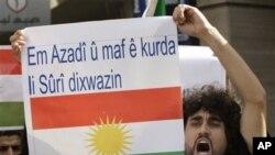 """Aktivis Kurdi yang mengecam pemerintahan Presiden Suriah Bashar Assad membentangkan poster yang bertuliskan """"Kami ingin kebebasan dan perlindungan hak warga Kurdi di Suriah"""" dalam sebuah demonstrasi di kedubes Suriah di Beirut, 23/10/2011."""