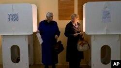 Dua warga Moskow di sebuah TPS untuk memberikan suara dalam pemilihan walikota Moskow, Minggu (8/9).