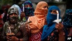 Activistas realizan una vigilia de protesta en India por la violación y asesinato de las dos adolescentes.
